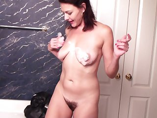 Guileful mommy Betsy Throbbing spreads her legs to play with a dildo